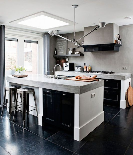 white + black kitchen with industrial lighting + thick concrete countertops + tolix stools