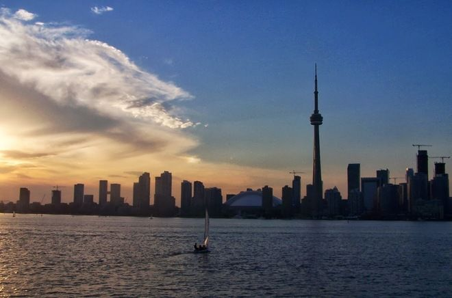 Date shot: June 20, 2013     A pretty cloud formation arches over this beautiful scene of Toronto's waterfront as seen from the island ferry.