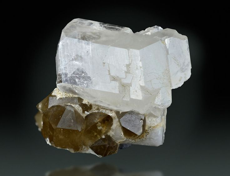 Phenakite, Be2SiO4, and smoky Quartz, Phenakite Mine, Khetchel village, Molo quarter, Momeik Township, Kyaukme District, Shan State, Myanmar. Largest crystal size: 25 mm. Blocky Phenakite xl, embellished by a few Smoky Quartz xls. Collection of the Natural History Museum Vienna. Copyright: © Harald Schillhammer
