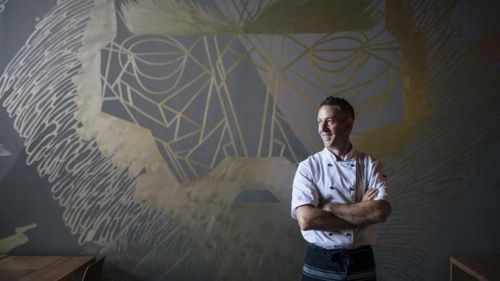 Co-owner of new paleo cafe, Elemental, Daniel Barrett, in front of the George Rose mural in the cafe.