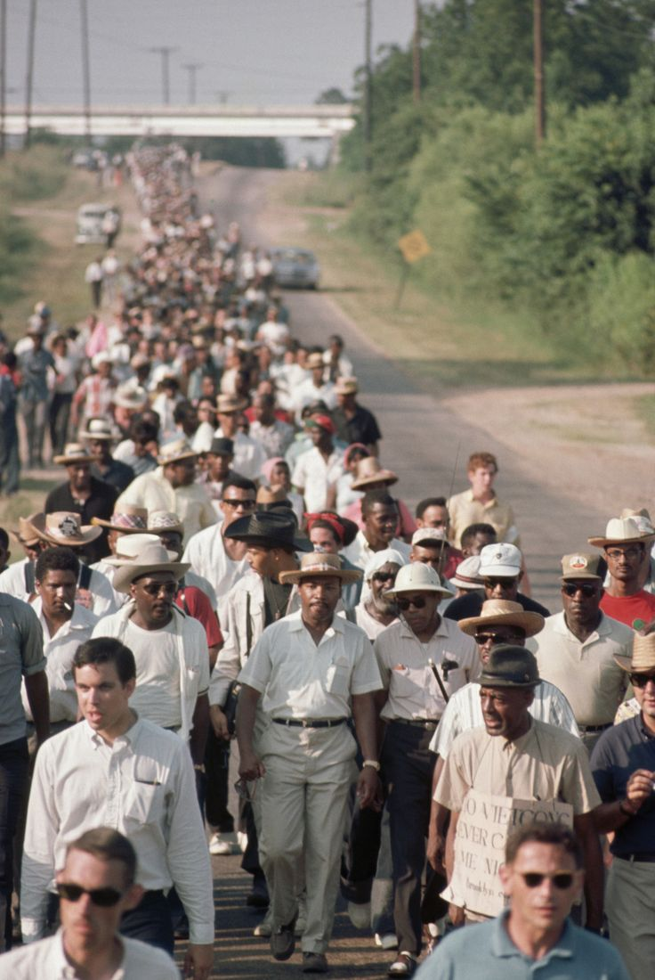 Dick Gregory and James Meredith walk alongside Martin Luther King Jr. on a rural road