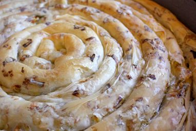 How to make Maznik (mahz-neek). This is a traditional Macedonian handmade pastry filled with crumbled white cheese, similar to feta. Before baking, we place a coin underneath the Maznik and when done, each family member is cut a slice. Before removing the slices, the tray with the Maznik is spun three times and the person that gets the slice with the coin underneath it, has a year of Good Luck!