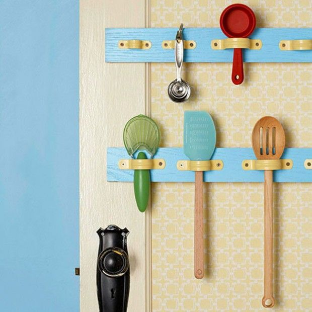OMG... what a great idea!  Use metal pipe clips inside kitchen doors to hang up serving spoons, spatulas & such!  This way they won't keep falling off the pegs.