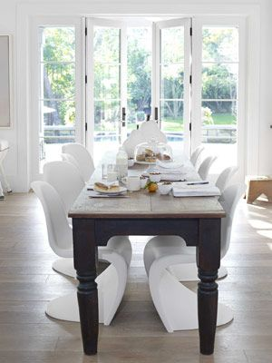"""Modern and Antique Dining Room--Verner Panton molded plastic chairs from Design Within Reach slide under a 10-foot-long antique table, """"narrow enough so you can really converse,"""" Hoefer says."""