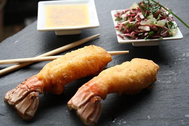 Les langoustines sont décortiquées, marinées dans de la poudre d'orange relevée au piment d'Espelette, et frites dans une pâte à tempura. Elles sont accompagnées d'une salade d'herbes et d'une vinaigrette aux fruits de la passion.