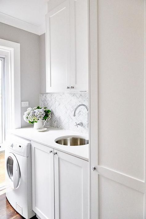 Small white laundry room features a front loading washer enclosed beside white shaker cabinets fitted with polished nickel knobs and a white quartz countertop fitted with a round metal sink paired with a wall mounted polished nickel gooseneck faucet fixed in front of gray marble herringbone backsplash tiles complementing white upper cabinets and gray walls.