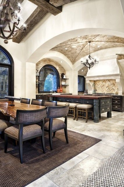 Mediterranean-style kitchen and open dining room  (via JAUREGUI Architecture Interior Construction)