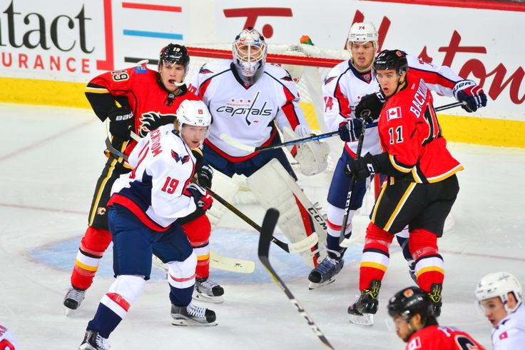 CALGARY, AB - OCTOBER 30: Calgary Flames Left Wing Matthew Tkachuk (19), Washington Capitals Center Nicklas Backstrom (19), Washington Capitals Defenceman John Carlson (74) and Calgary Flames Center Mikael Backlund (11) battle for position around the net guarded by Washington Capitals Goalie Braden Holtby (70) during a game between the Calgary Flames and the Washington Capitals on October 30, 2016, at the Scotiabank Saddledome, in Calgary AB. Washington defeated Calgary 3-1. (Photo by Jose…