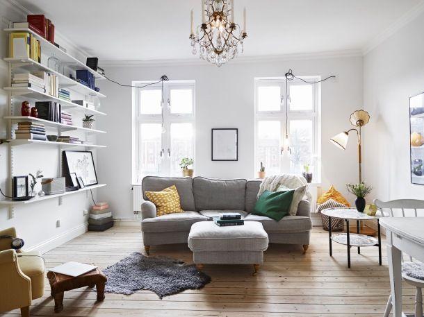 Szara kanapa z materiału i zółte i zielone poduszki