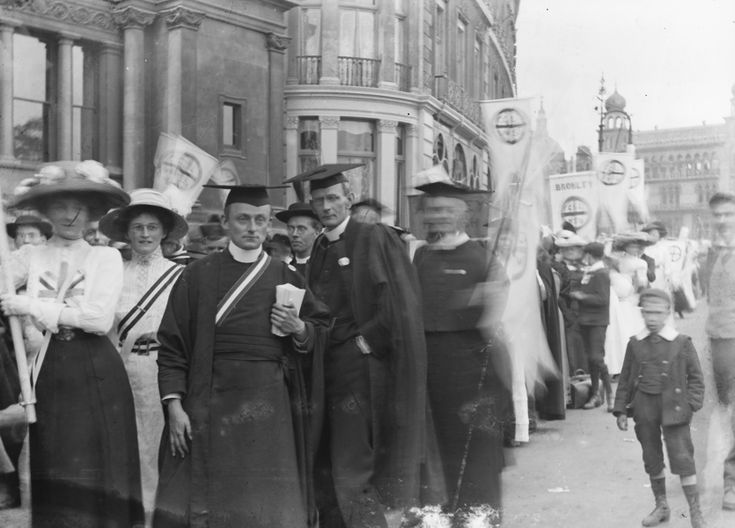 Suffragette procession, including two men in the foreground wearing mortar boards and gowns. A banner on the right reads 'Bromley'.