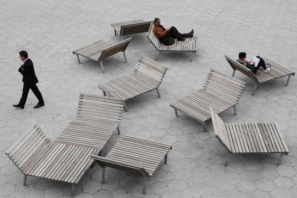 Un uomo se ne va mentre altri due leggono sulle panche di legno lungo l'East River a New York