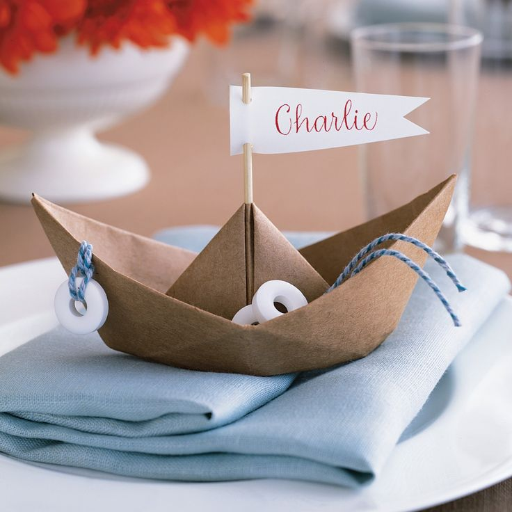 Create these easy and fun DIY place cards that are folded in the shape of a boat for younger  guests.