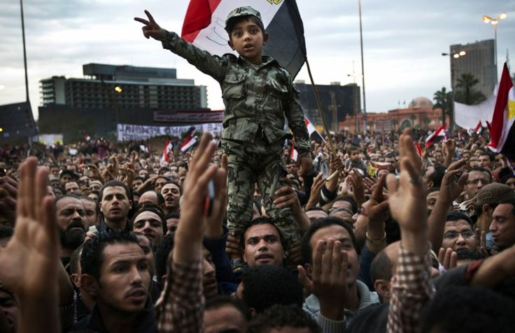 The Fight for Tahrir Square  04 February 2011 by Jan Dago    A boy is dressed in a military uniform at a demonstration in Tahrir Square in Cairo as a symbol of the opposition's trust in the Egyptian military. The anti-government protestors demanded that President Hosni Mubarak step down peacefully, but clashes broke out between them and Mubarak supporters in Tahrir Square.