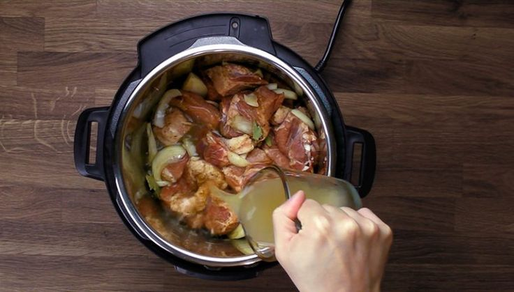 Easy Instant Pot Carnitas Recipe (Pressure Cooker Carnitas): pouring chicken stock in Instant Pot Electric Pressure Cooker