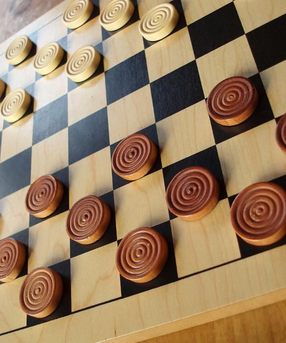 traditional game of strategy: counters on a wooden draughts board - free stock photo from www.freeimages.co.uk