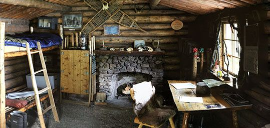 View of the rear of Dick Proenneke's Alaskan cabin showing his bunk, the fireplace and his writing desk.