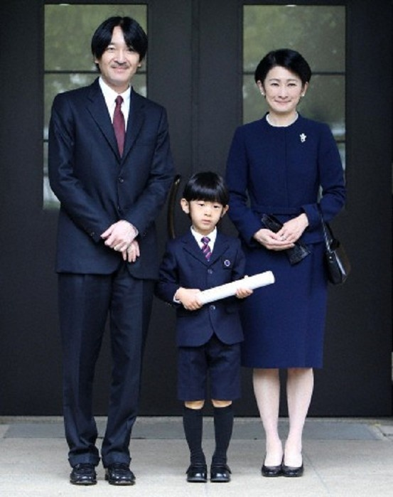 Japan's Prince Hisahito (C) holding a certificate of graduation, accompanied by his father Prince Akishino (L) and mother Princess Kiko, at Ochanomizu University affiliated kidergarten in Tokyo 14 March 2013