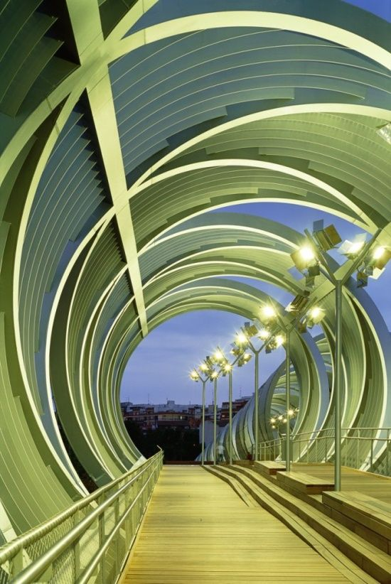 Arganzuela Footbridge, Madrid, Spain.  The footbridge enables people to cross from one side of the park to the other while also providing direct access to the park below. Cone like in structure, the bridge has two interlocking metal spirals, wrapped by a metallic ribbon. Spaced wooden slats make up the floor of the bridge, allowing the rays of the sun to penetrate through to the park below. Shaded during the day, the promenade becomes luminous at night