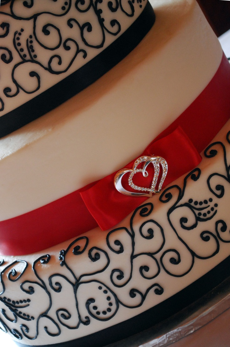 3 tiered oval Wedding cake with black scroll piping, red ribbon and double heart bling - toptierweddingcakes.dotphoto.com