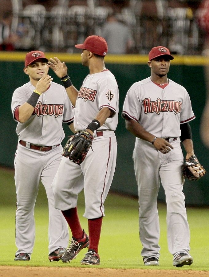 Chris Young #24 congratulates Gerardo Parra #8 and Justin Upton #10 of the Arizona Diamondbacks after they defeated the Houston Astros on August 18, 2012 at Minute Maid Park in Houston, Texas.