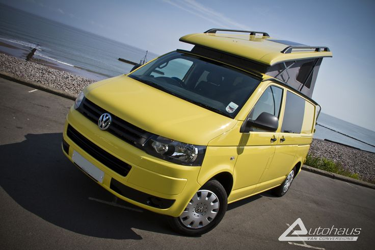 A VW T5 Camper in Sunny Yellow from Autohaus. This on is configured as a 'Camelot' which features two single RIB rock n roll beds that can be pushed together to form a double, a rear elevating Reimo roof, a full kitchen with sink, hob and fridge. The Camelot also features an onboard toilet for the cold nights when you don't fancy venturing to the toilet block (or a nearby hedge!).