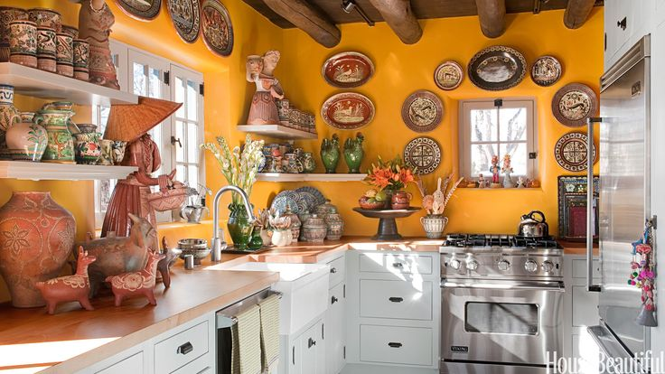 The sunbaked yellow paint was custom-mixed and sets off a semicircle of Petatillo-style plates, topped by a platter from Capula, Mexico, above the Viking Professional Series range. Refrigerator and dishwasher also from Viking Professional Series. The Hansgrohe faucet has been discontinued in favor of a similar model, the Talis S HighArc. Whitehaus fireclay sink. Custom blue paint on cabinetry. Hardware from House of Antique Hardware.   - HouseBeautiful.com