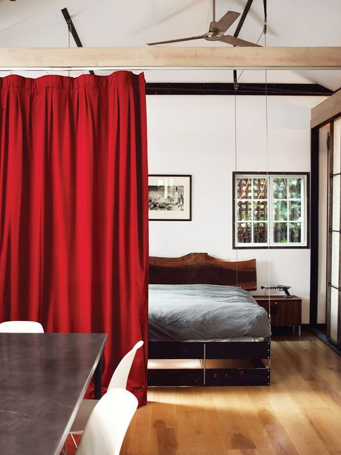 In a 580-square-foot Hollywood bungalow, a heavy velvet curtain slides across to shield the bedroom from the rest of the open space, creating privacy without walls. Photo by Joe Pugliese.  Photo by Joe Pugliese.   This originally appeared in How to Design with Red.