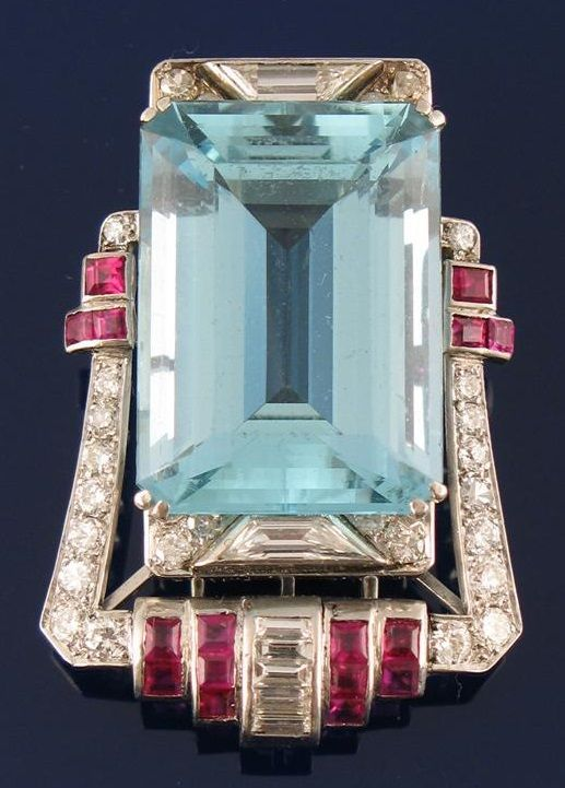 An Art Deco aquamarine, diamond and ruby clip, the step cut aquamarine measuring 25 x 18 x 12mm in a calibre ruby, baguette, brilliant and trapezoid cut diamond set frame.