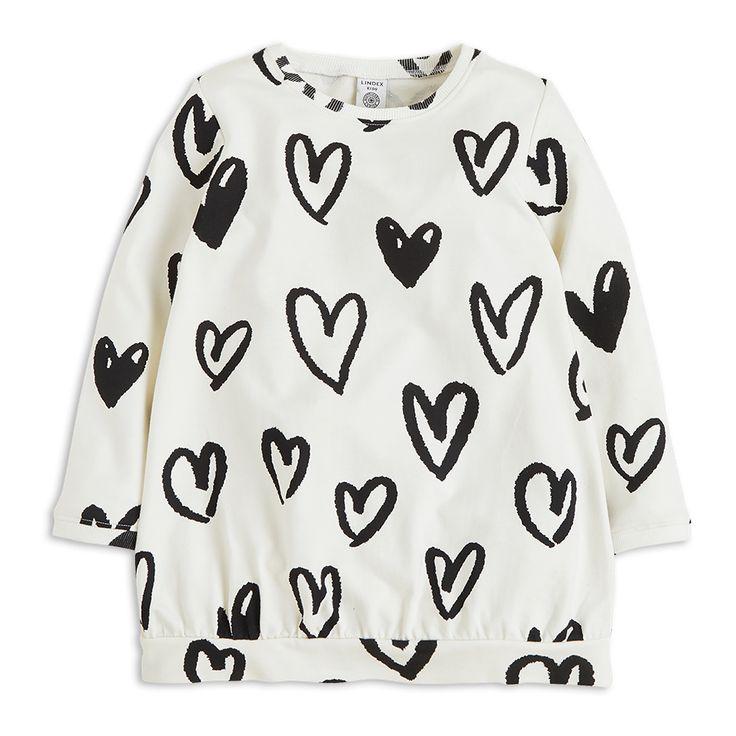 En skön tunika i sweatshirtkvalitet tillverkad i ekologisk bomull. Den kommer i en snygg benvit färg, översållad med svarta hjärtan. Matcha med svartvit-randiga leggings för en cool mönstermix.