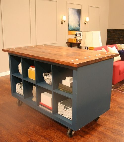 Love this idea! Take two IKEA Expedit bookcases, frame in MDF, paint, attach casters, and bolt some stained 2×10's to the top. Designed by the amazing Justine Taylor.