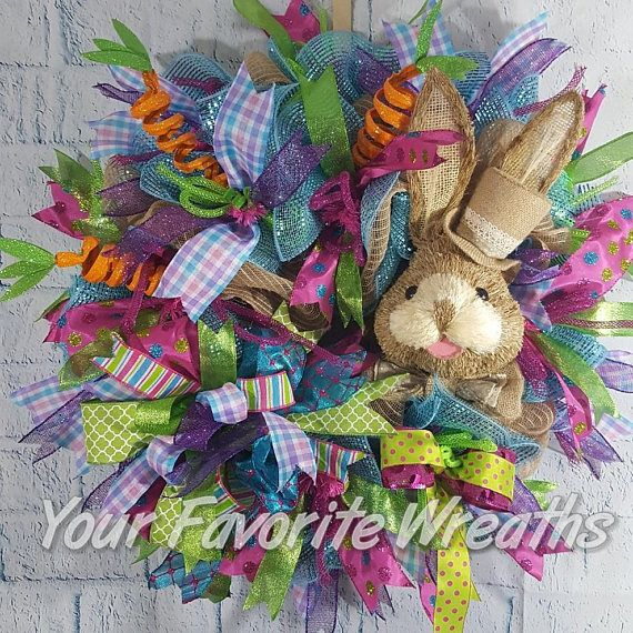 A beautiful 24 deco mesh Easter wreath.It is very well decorated with lots of spring colored ribbon.Has a cute sisal 14 bunny head with a top hat. 3 orange carrots balances the left side of the wreath.