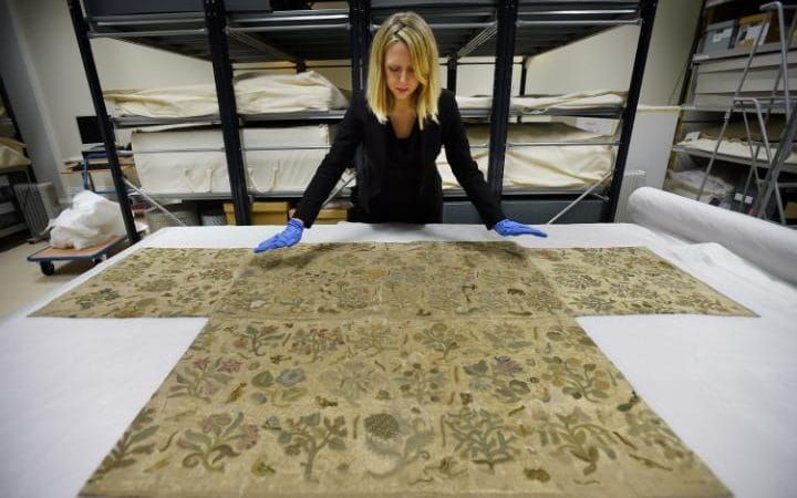 Dress historian Eleri Lynn, left, with the Bacton altar cloth. The pattern is strikingly similar to a bodice worn by the Tudor queen in a portrait, right