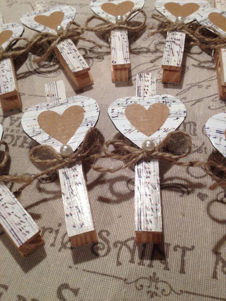 Chiudi pacco con mollette da bucato in legno recuperate. I cuori sono di una scatola di cartone porta - caffè ricoperti con  alcune pagine di un vecchio spartito, con la carta di un sacchetto recuperato, sono stati fatti gli altri cuori.