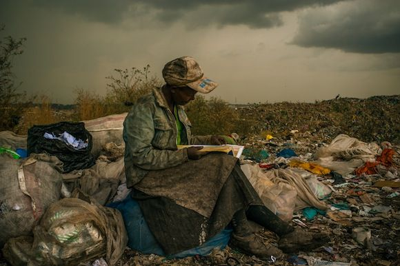 "On hope and human dignity.Micah Albert, USA, Redux Images,1st Prize Contemporary Issues Single.Taken on 03 April 2012 in Nairobi,Kenya.Pausing in the rain,a woman working as a trash picker at the 30-acre dump,which literally spills into households of one million people living in nearby slums, wishes she had more time to look at the books she comes across.She even likes the industrial parts catalogs.""It gives me something else to do in the day besides picking [trash],""she said."