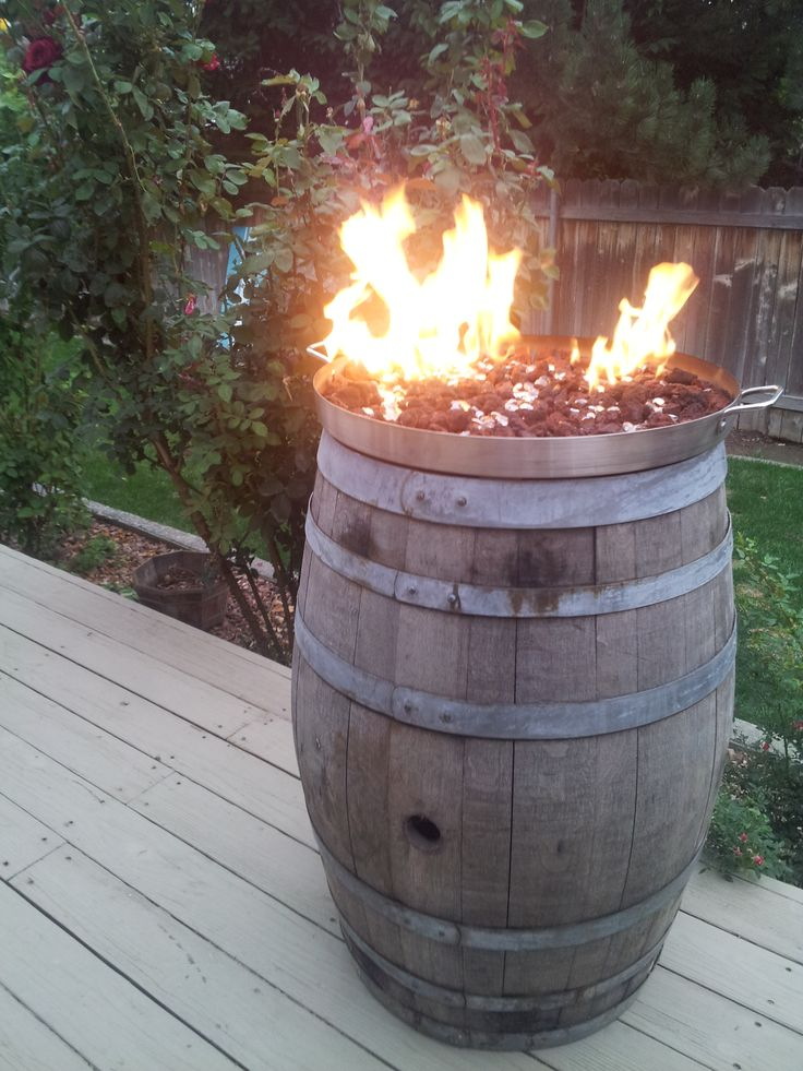 Wine barrel fire pit. Cooking pot from Mexican flea market, homemade copper burner, 15lb propane tank. Finished off with lava rock and marbles.