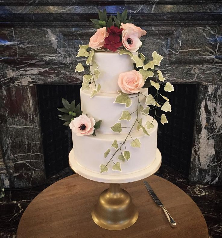 A bit of a rubbishy picture but hey ho! Here's Saturday's wedding cake set up at @the_landmark_london // pristine white sugarpaste finished with handcrafted sugar flowers: blush anemones, quicksand roses, chocolate cosmos, trailing ivy and olive // what you can't see in this pic were the 8 additional cuttings cakes to feed the 400 guests for dessert!