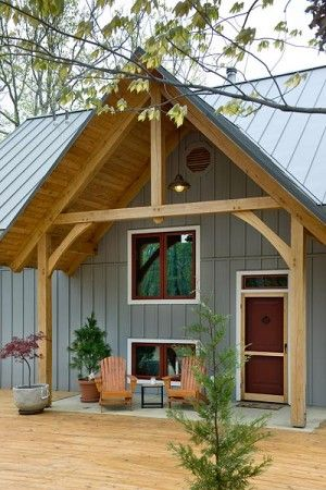 A king post truss creates a covered entryway and hints at what is to come. Fiber-cement siding with a board-and-batten look adds visual inte...