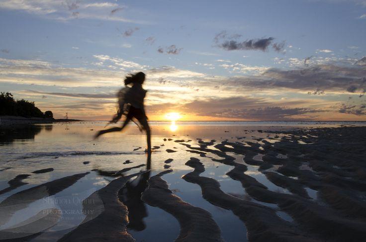 "shanonquinnphotography.com ""Faery Sunlit Capture"" Heron Island Great Barrier Reef sunset silhouette girl running on beach through water. Movement."