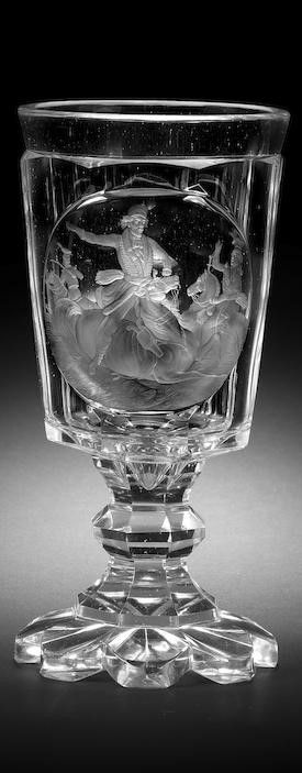 A Bohemian engraved goblet, dated 1845 The cup-shaped bowl with faceted base, decorated with a continuous landscape scene of a fox hunt, divided into two scenes by trees, one showing a hunter standing holding his rifle with two dogs retrieving a fox before him, the reverse showing two dogs chasing a fox, set on a collar above an octagonal faceted baluster stem, over an octagonal faceted foot inscribed den 20:ten October 1845, star-cut base, 21.5cm high