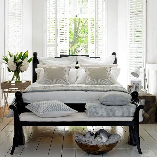 Relaxed neutral bedroom: Texture has been created using carved wood, rattan furniture and linen fabrics. Dark-wood furniture against the white walls and floors creates a focal point in the room. Piano stool and bed from Lombok; Throw from The White Company; Cushion covers from Zara Home. Photograph by David Brittain