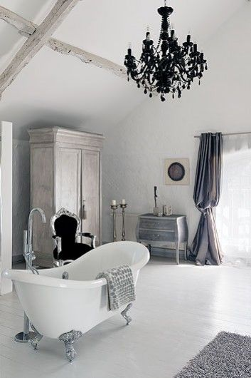 Freestanding roll-top bath, chandelier, and lots of silver.