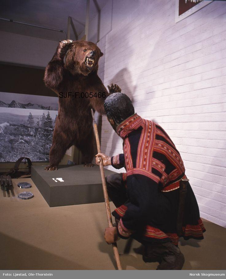 Jaktscene i Norsk Skogbruksmuseums jaktutstilling, som ble åpnet i 1972.  Fotografiet viser utstillingen slik den så ut i 1983.  Hovedmotivet her er en montasje som viser bjørnejakt med spyd.  Jegeren er en mannsfigur som sitter på huk med et spyd i hendene.  Han har støtt den bakre enden av spydskaftet mot underlaget og holder jernspissen skrått oppover.  Foran ham står en brunbjørn på bakbeina med framlabbene hevet til slag og glefsende kjeft.  Det man forsøker å illustrere er en…