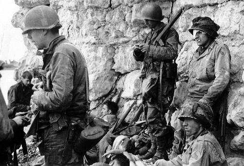 Sous le Wn 60 au pied de la falaise de Colleville sur Mer; Omaha Beach secteur Fox Red à droite de Fox Green et de F-1  secteur de la L/16th IR de la 1st US ID, Ces soldats sont à l'abri du feu allemand.  Les deux GI les plus à droite appartiennent à la 29th US ID (Blue and Grey) les patches d'épaule ne sont même pas censurés ; sans doute des hommes des 4 sections de la E/116th IR ayant échoué dans ce secteur (au lieu d'Easy Green).