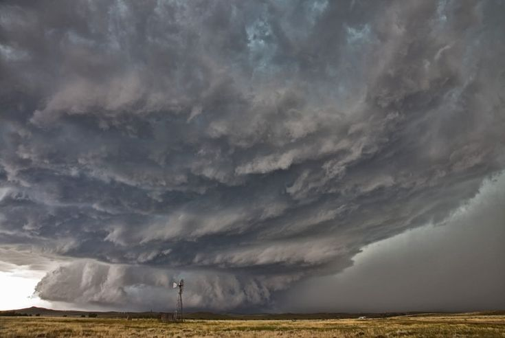 Tornadic supercell thunderstorm over a plain in Mycroft, Wyoming, US.  Supercell thunderstorms rotate with immense energy, causing a strong updraft and severe weather, including tornadoes, hail, heavy rain, lightning and heavy winds. Inside these severe long-lived storms the wind speed and direction changes with height.