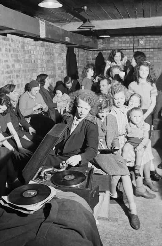 A young woman plays a gramophone in an air raid shelter in north London during 1940 ~