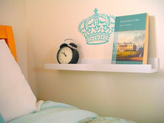 IKEA RIBBA picture ledge as a nightstand for a bed by a wall