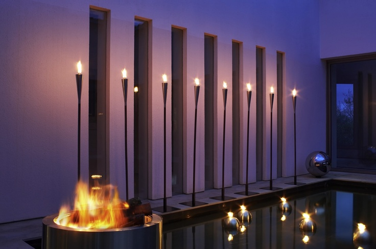 Light up, stay warm, impress your guests with outdoor stainless steel tiki torches. A simple idea with a contemporary look in this sleekly designed backyard. The concrete fire bowl is is simple and easy to operate.