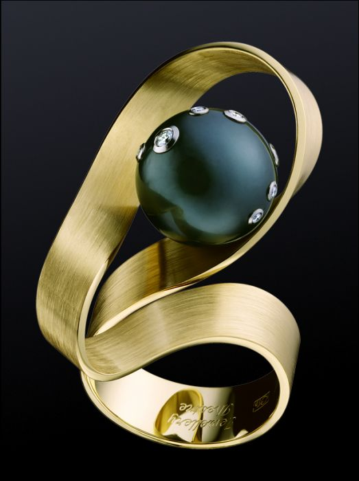 Gold and black pearl ring with inset diamond accents.