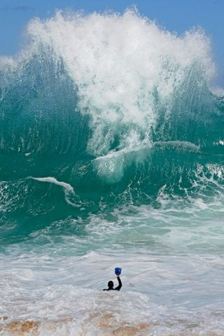 Photographer Clark Little facing a giant wave with his camera, in Oahu, Hawaii.  A photographer wades into the ocean to capture the beauty o...