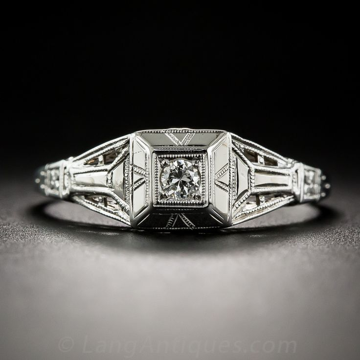 A small diamond sparkler shines solo from atop a decorative square beveled crown supported by complimentary tapered open shoulders in this sweet and striking original Art Deco engagement ring, crisply die-struck and hand-finished in gleaming 18K white gold - circa 1920s-30s. Currently ring size 9 1/2.
